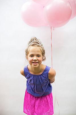 Smiling girl wearing tiara holding pink balloons - p555m1409066 by Shestock