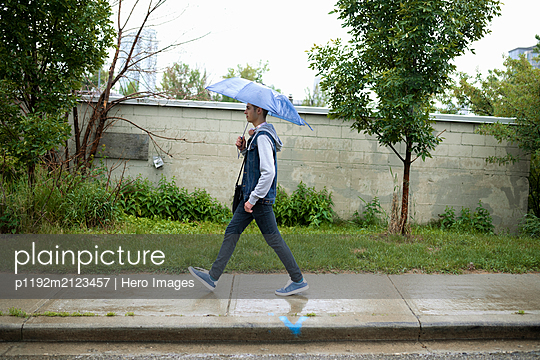 Young man with blue umbrella walking on wet sidewalk - p1192m2123457 by Hero Images