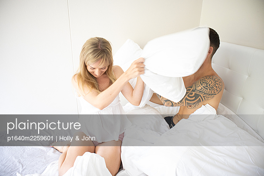 Couple has a pillow fight in the bed - p1640m2259601 by Holly & John