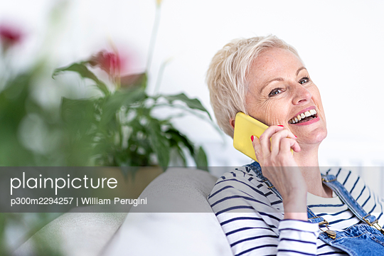 Smiling mature woman talking on smart phone at home - p300m2294257 by William Perugini