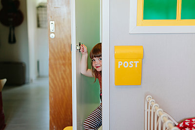 Girl peeking through door - p312m2191167 by Matilda Holmqvist