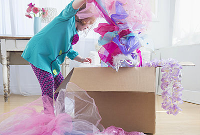 Caucasian girl unpacking dress-up clothes from box - p555m1412550 by JGI/Jamie Grill