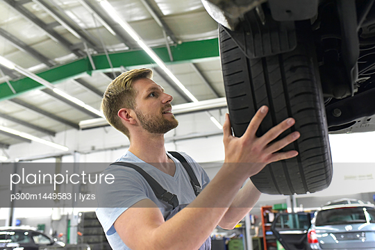 Car mechanic in a workshop changing car tyre - p300m1449583 by lyzs