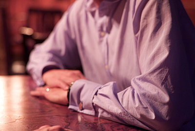 Man with dress shirt sitting at pub table with hands overlapping. - p1072m829547 by Tracy Jean Shields