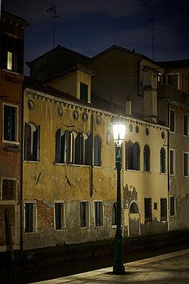 Straßenlaterne vor einer Häuserzeile bei Nacht - p1312m1575188 von Axel Killian