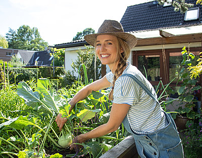 Woman working in her garden - p1678m2258833 by vey Fotoproduction