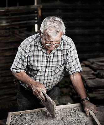 Stonemason working on stone - p300m1588046 von Christian Vorhofer