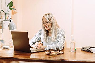 Happy senior taking online consultation through laptop at home - p300m2240471 by Eloisa Ramos