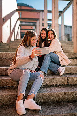 Smiling teenage girl taking selfie with friends while sitting on steps in city - p300m2252058 by LUPE RODRIGUEZ
