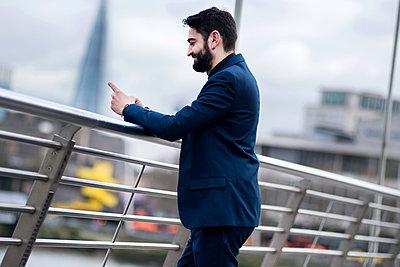 Businessman standing on footbridge reading smartphone text, London, UK - p429m1135358f by Bonfanti Diego