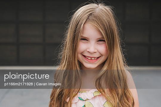 Closeup of a young girl in front of a garage door - p1166m2171928 by Cavan Images