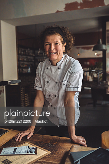 Portrait of smiling mature chef standing in restaurant - p426m2212208 by Maskot