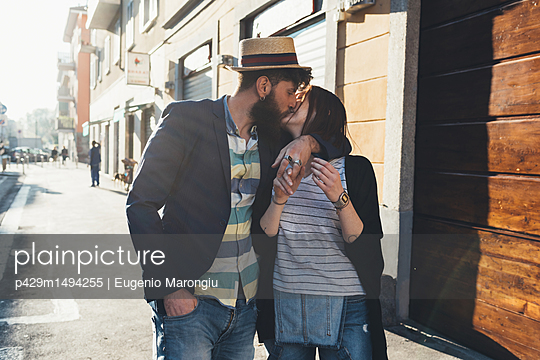 Romantic couple kissing on sunlit street - p429m1494255 by Eugenio Marongiu