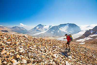 Side view of backpacker hiking over rocky terrain. - p1166m2153468 by Cavan Images