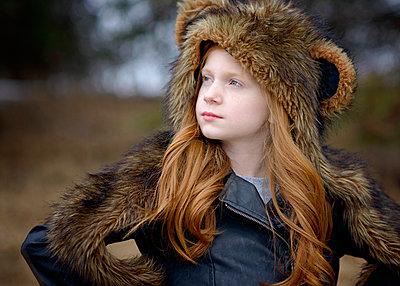 Young Girl Long Red Hair Wearing Bear Spirit Hood - p1166m2208456 by Cavan Images