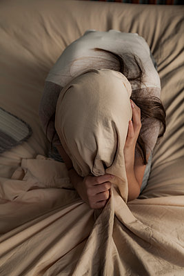 Teenage girl hiding under bed sheet. - p397m1154811 by Peter Glass