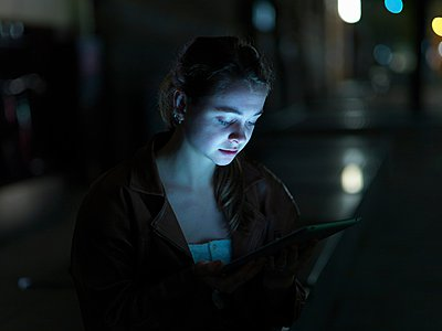 Young woman using digital tablet, outdoors, at night, face illuminated - p429m1052742 by Elke Meitzel