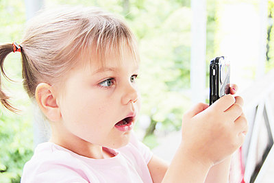 Toddler playing with cell phone - p429m712398f by Sigrid Gombert