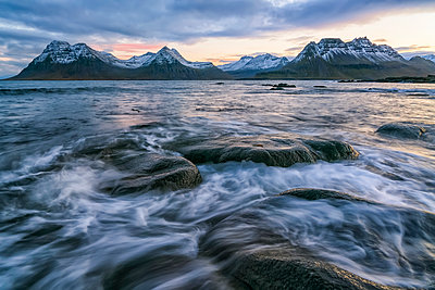 Sunset over the mountains of the Strandir Coast, Iceland as the surf pounds the shoreline; West Fjords, Iceland - p442m2004283 by Robert Postma