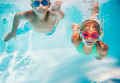 Caucasian children swimming underwater in pool - p555m1421659 by JGI/Jamie Grill