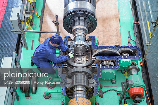 Overhead view of engineer inspecting gears on generator in turbine hall of nuclear power station during outage - p429m2058288 by Monty Rakusen