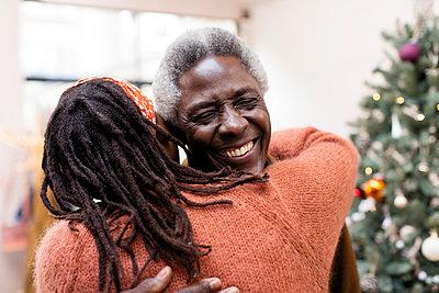 Happy senior couple hugging near Christmas tree - p1023m1575865 by Sam Edwards