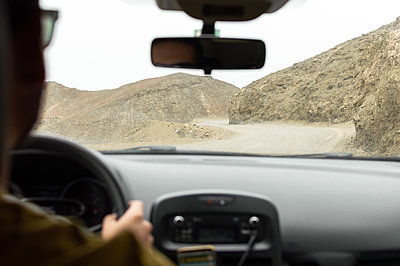 Man driving a car on a mountain road of the desert. Road trip. - p1166m2235423 by Cavan Images