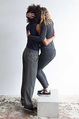 Blonde woman on pedestal embraces her girlfriend - p1301m2020248 by Delia Baum