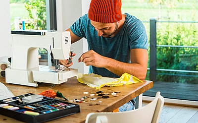 Young man at home using sewing machine - p300m1059020f by Uwe Umstätter
