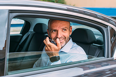 Businessman sitting on a backseat of a car using smartphone and looking around - p300m2139765 by Jesús Martinez