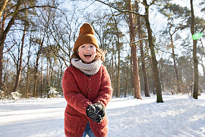 Curious boy in warm clothing playing with snow during winter - p300m2281942 by Frank van Delft
