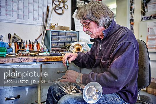 Instrument maker repairing trumpet in workshop - p300m1157271 by Dirk Kittelberger