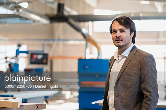 Confident young businessman staring while standing at industry - p300m2250760 by Daniel Ingold