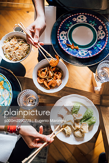 Couple eating food while sitting by dining table at home - p300m2290779 by Eugenio Marongiu
