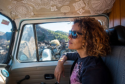 Thoughtful woman looking away while wearing sunglasses in camper trailer - p1166m1507847 by Cavan Images