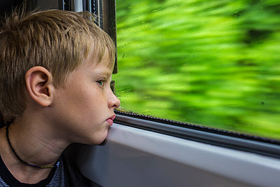 Close-up of thoughtful boy looking through window while traveling in train  - p1166m2068114 by Cavan Images