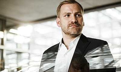 Portrait of businessman in office building - p300m2206959 by Sandro Jödicke