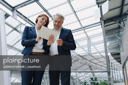 Smiling businessman and businesswoman using tablet in modern office building - p300m2156348 by Joseffson