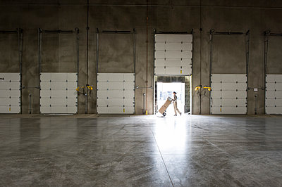 A warehouse worker with a hand truck walking past an open loading dock door in a large distribution warehouse. - p1100m2002264 by Mint Images