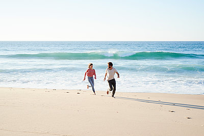Young couple running on beach - p1124m1508606 by Willing-Holtz