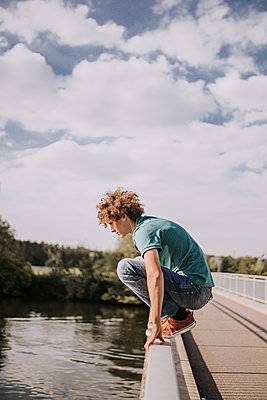Young man on bridge railing, portrait - p1267m2259705 by Jörg Meier