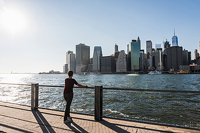 USA, Brooklyn, back view of woman  looking at Manhattan skyline - p300m1205834 by Uwe Umstätter