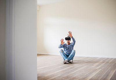 Man in empty apartment wearing VR glasses - p300m1460013 by Uwe Umstätter