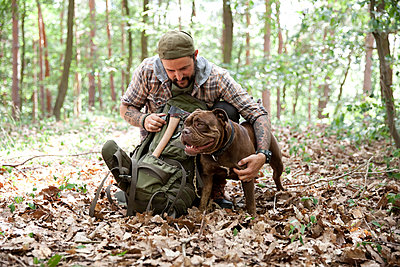 Man with dog in forest - p300m1499475 by Michelle Fraikin