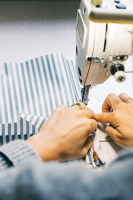 Close-up of woman using sewing machine - p300m2029646 by Visualspectrum