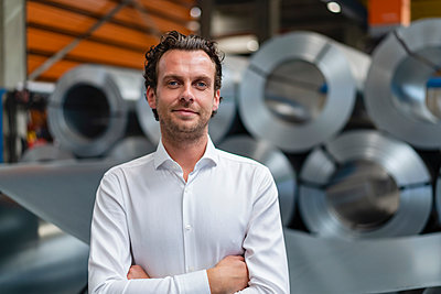 Confident businessman with arms crossed standing at factory - p300m2293345 by Daniel Ingold