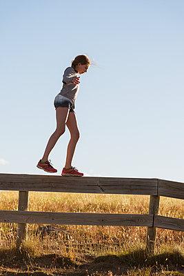 Girl walking on wooden fence - p312m1495697 by Hans Berggren