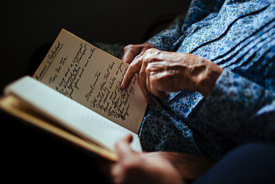 Older woman reading handwriting to granddaughter - p555m1408712 by Shestock