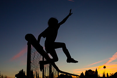 Silhouette sporty girl jumping over fence during dusk against sky - p1166m1474312 by Cavan Images