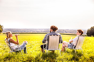 Friends sitting on camping chairs in rural landscape - p300m2069780 by Jo Kirchherr